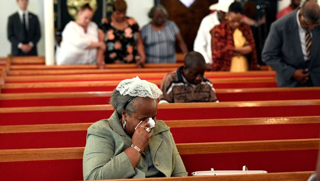 A woman weeps during mass at Galilee Baptist Church held in the wake of the shooting at the Art All Night Festival in Trenton, NJ early Sunday, June 17, 2018.