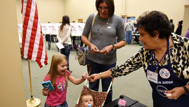 """Volunteer Juanita Valdez, right, hands an honorary """"I voted"""" sticker to Bristol Whitlock, 3, after her mother Natalie voted with Bristol and son Taylor, 1, at the Harmony Market polling place in Fort Collins on Election Day Thursday, Nov. 4, 2014."""