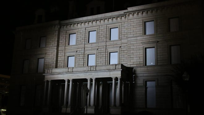 """People watch """"A Tale of Five Flags,"""" a visual video mapping story presented on the front of the Artel Gallery over the weekend."""