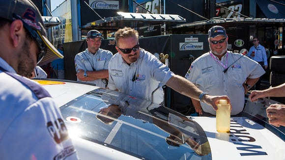 NASCAR official Jon Ryan grabs a bottle of lubricant for car 2, Brad Keselowski's Miller Lite Ford at the Nationwide Series race Sunday November 9, 2014 in Avondale.