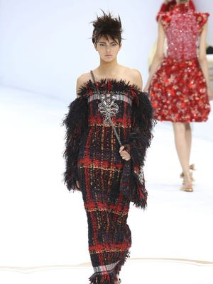 """Kendall Jenner of """"Keeping Up With The Kardashians"""" fame appears in a punk-inspired tweed off-the-shoulder dress sprouting with feathers."""