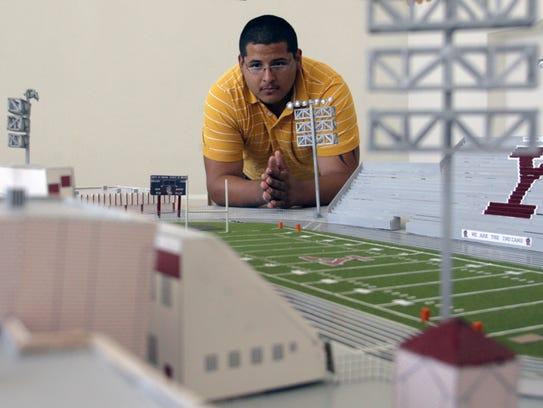 In this June 12, 2010 file photo Ysleta High School graduate Jesse Hinojos looks at his 1/8-inch scale model of Ysleta High School's Hutchins Stadium.