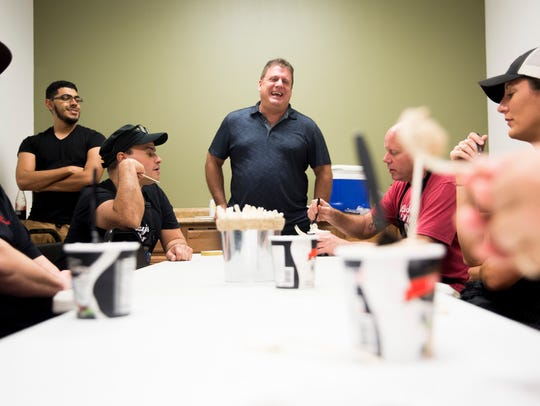 Joe Araneo, center, shares pints of his company's product,
