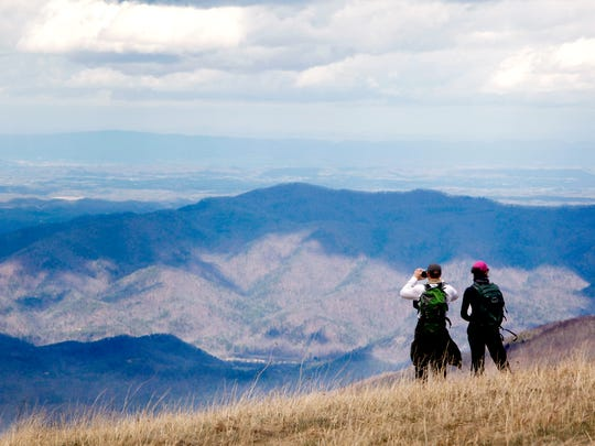 Max Patch is a popular spot in Madison County for visitors to take classic Blue Ridge Mountain views. Here, Rusty and Sara Booth, of Ohio, take in the 360-degree mountain views in March 2017.