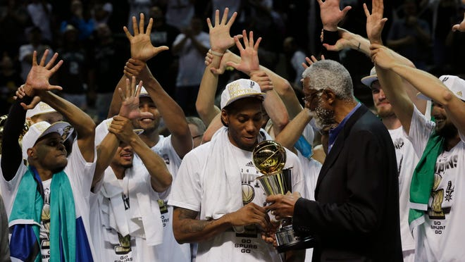 Bill Russell (right) presents the MVP award to Spurs forward Kawhi Leonard after San Antonio's 104-87 victory over Miami in Game 5 of the NBA Finals on Sunday. The Spurs won their fifth NBA championship.
