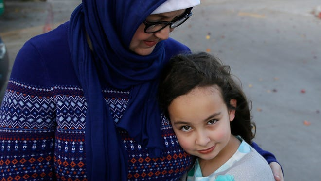 Sofia Yassini, 8, right, gets a hug from her mother Melissa Yassini after posing for a photo outsider a mosque in Richardson, Texas, Friday, Dec. 11, 2015.