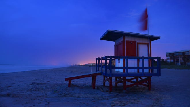 At dawn the red warning flags blow in the wind at a boarded up lifeguard station in Cocoa Beach. The hotels were empty and streets almost deserted beachside early Saturday morning.