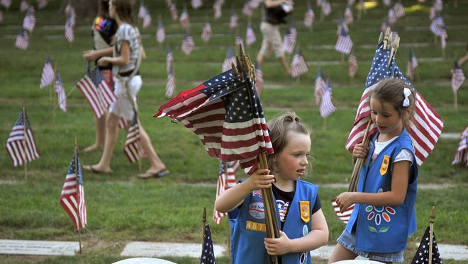 Girl Scouts place flags on headstones at the Grand Rapids Veterans State Cemetery in Grand Rapids, Michigan, in 2012.