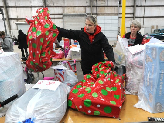 """Volunteers Teri Dillon, left, and Donna Watkins organize Christmas gift donations collected by the Taylor County Child Welfare Board to serve 290 abused or neglected children in their program in 2016.  The """"Miracle on Vine Street,"""" the board's annual toy drive, pairs children in CPS care with community donors who buy the gifts."""
