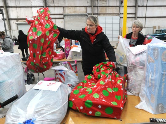 "Volunteers Teri Dillon, left, and Donna Watkins organize Christmas gift donations collected by the Taylor County Child Welfare Board to serve 290 abused or neglected children in their program in 2016.  The ""Miracle on Vine Street,"" the board's annual toy drive, pairs children in CPS care with community donors who buy the gifts."