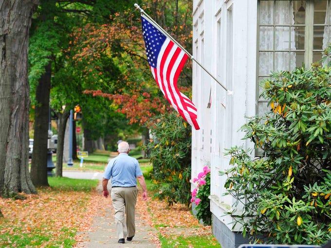 A pedestrian walks down a street in Warren, PA September,