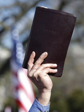 Opponent of gay marriage holds up a Bible in front of the Supreme Court.