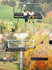 Visitors take sight-seeing to the air as they look at fall colors from chairlifts at Granite Peak in Rib Mountain.