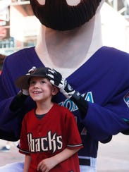 Connor Carmack, 6, poses with a giant Mark Grace mascot before Friday's Diamondbacks game.
