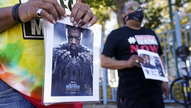 "A portrait of the late actor Chadwick Boseman as the character T'Challa in the 2018 film ""Black Panther"" is held by a participant in a news conference celebrating his life Saturday in Los Angeles. Boseman died Friday at 43 after a four-year fight with colon cancer."