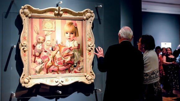 "Visitors look at ""Rosie's Tea Party"" by Mark Ryden"