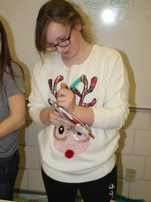 Clear Creek Amana sixth grader Madeline Downes fills out a gift tag during Wrappin for a Cause Thursday, Dec. 17.