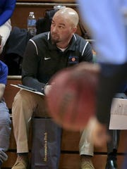 Assistant Coach Damian Davies sits courtside before the Leechburg High School girls basketball team plays in a league playoff game in Bellevue, Pennsylvania, on Friday, Feb. 17, 2017.