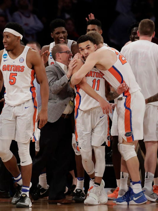 Florida players celebrate after a last second shot by guard Chris Chiozza (11) to beat Wisconsin in overtime of an East Regional semifinal game of the NCAA men's college basketball tournament, Saturday, March 25, 2017, in New York. Florida won 84-83. (AP Photo/Julio Cortez)