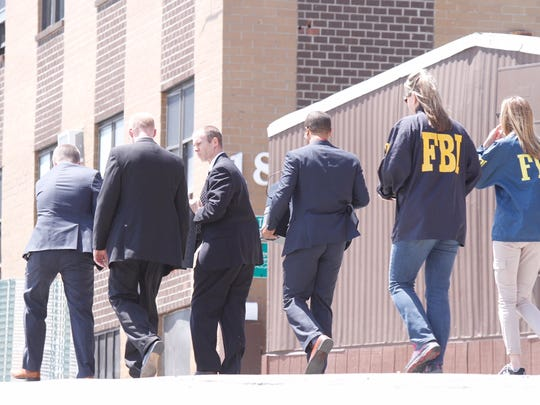 Law enforcement officials take part in a search Thursday at 16A Getzil Berger Blvd. in Kiryas Joel, part of the United Talmudical Academy.