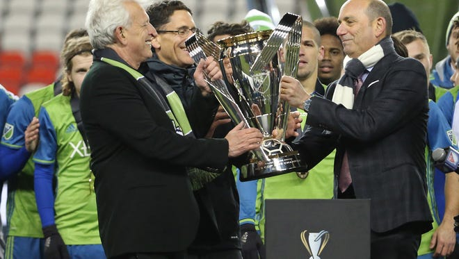 MLS commissioner Don Garber presents the Philip F. Anschutz Trophy to Seattle Sounders owner Joe Roth (L) and Sounders majority owner Adrian Hanauer (2-L) after the Sounders defeated Toronto FC in the 2016 MLS Cup at BMO Field.