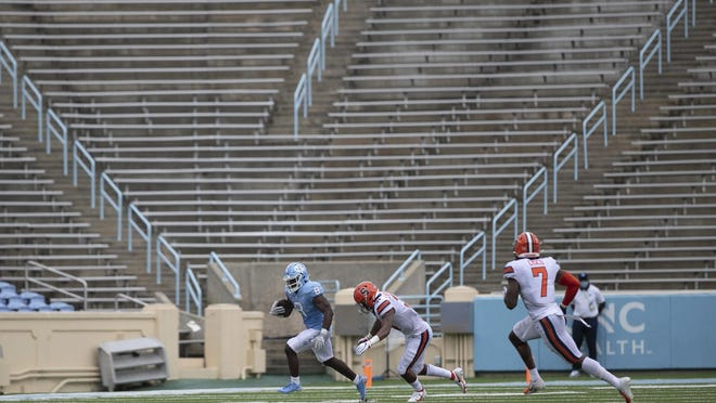 North Carolina running back Michael Carter, left, scampers past Syracuse linebacker Geoff Cantin-Arku during Saturday's season opener at empty Kenan Stadium.