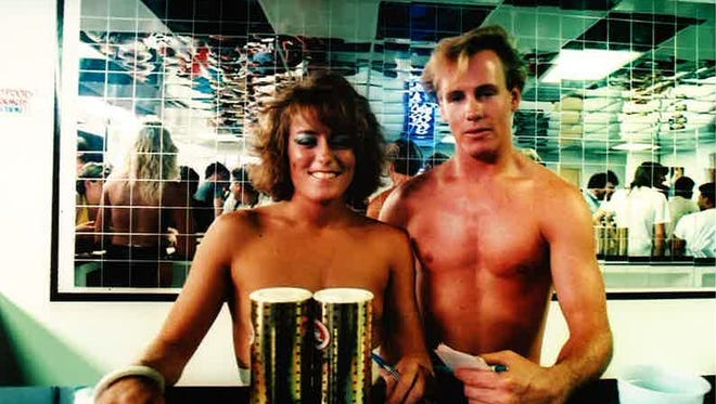 "A waitress and ""token male waiter"" pose on opening day at Debbie Duz Donuts, July 29, 1989."