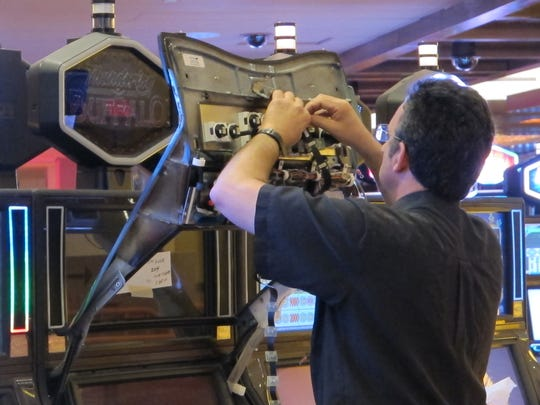 A worker adjusts a slot machine at Tropicana Casino and Resort in Atlantic City, part of a $50 million renovation project due to be completed by Memorial Day weekend.