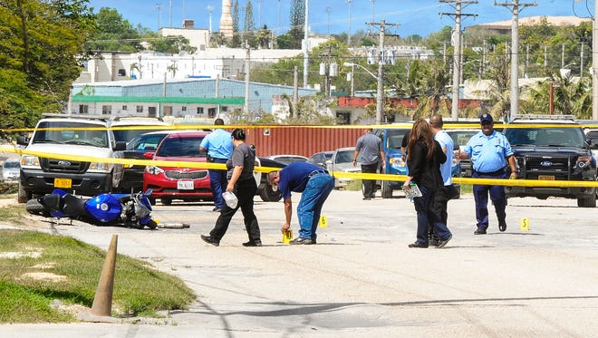 Guam Police Department officers conduct an investigation of a shooting in Harmon on June 15.
