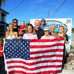 Holding one of the flags donated to Capri Community Inc. are, from left, are Axton and his mother, Evelim Middlebrook, Debbie Cooper, Annie Cooper, and Karen Cooper; second row, Beau Middlebrook holding son, Christopher, Mike Cooper and Mitch Cooper. In back is Steve Cooper.