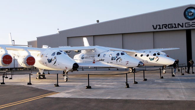 FILE - In this Sept. 25, 2013, file photo, the first SpaceShipTwo is seen suspended at center beneath its twin-fuselage mother ship at the Virgin Galactic hangar at Mojave Air and Space Port in Mojave, Calif. Virgin Galactic will roll out a new copy of its space tourism rocket Friday, Feb. 19, 2016, as it prepares to resume flight testing for the first time since a 2014 accident destroyed the original and killed one of its two pilots. (AP Photo/Reed Saxon, File)