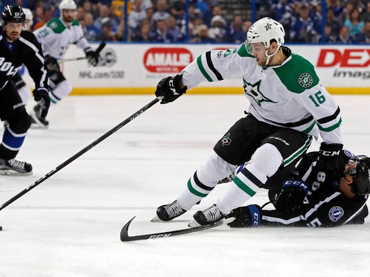 Dallas Stars' Jason Dickinson fends off the defense of Tampa Bay Lightning's Jake Dotchin during the first period of an NHL hockey game Sunday, April 2, 2017, in Tampa, Fla. (AP Photo/Mike Carlson)