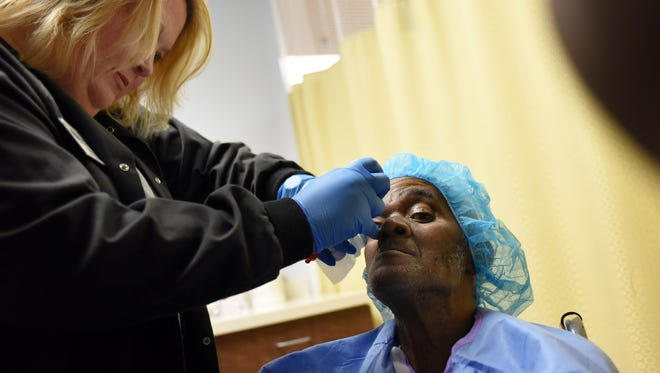 Stephanie Hall, R.N., gives Hattiesburg patient Tonnie Floyd eye drops before a cataract removal surgery Oct. 23 at Souther Eye Center. The center gave 5 cataract removal surgeries in celebrating the 12th anniversary of their National Make a Difference day.