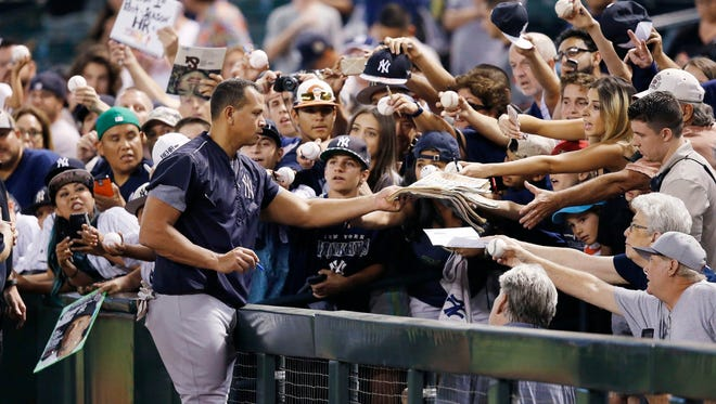 New York Yankees' Alex Rodriguez signs autographs for fans prior to a baseball game against the Arizona Diamondbacks Tuesday, May 17, 2016, in Phoenix.