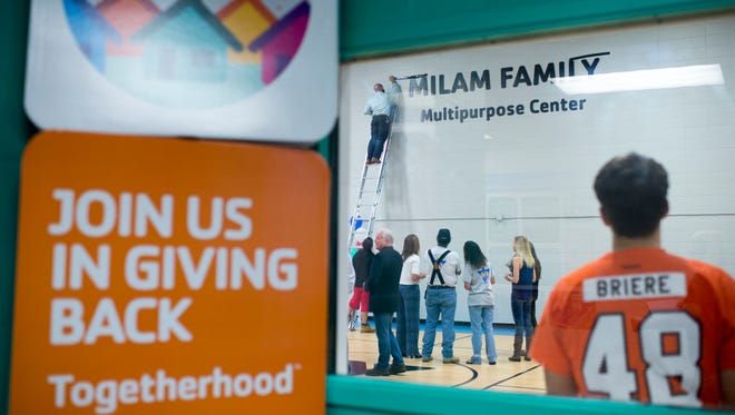 Guests watch the Milam Family Multipurpose Center name unveiling Thursday at the YMCA in Vineland.