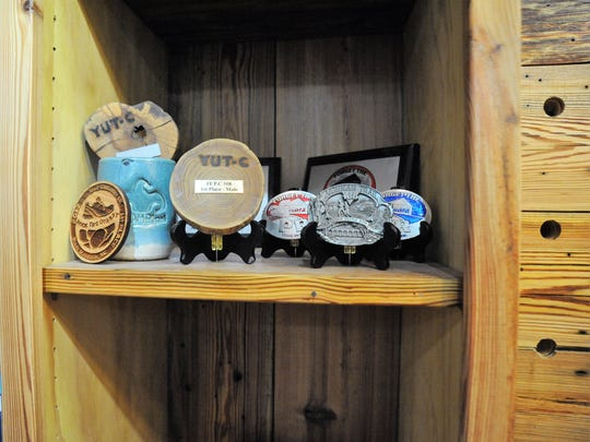 Trophies and belt buckles from some of the over 50 ultramarathons Shaun Pope has run in his career fill the shelves at Vertical Runner Black Mountain.