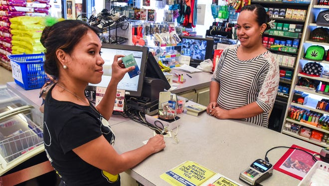 In this Feb. 21 file photo, Jayleen Kenneth, 35, holds up a pack of cigarettes after making a purchase from cashier Melody Mori at the Maxi Mart II store in Tamuning. Guam's tobacco tax is increasing as part of the fiscal 2019 budget law.