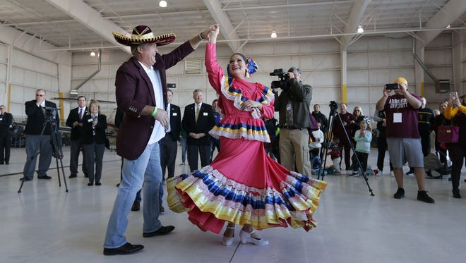Arizona State head football coach Todd Graham dances with a folklorico dancer after ASU arrived at El Paso International Airport on Monday, December 25, 2017. ASU plays North Carolina State in the Hyundai Sun Bowl on Friday, December 29, 2017.
