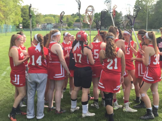 The Red Hook girls lacrosse team huddles during its