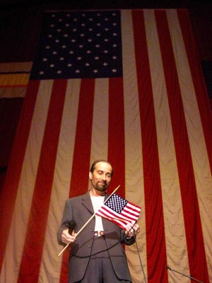 """Country music performer Lee Greenwood admires an American flag handed to him after his performance of """"God Bless the U.S.A."""" on Sept. 18, 2001, at the former Veterans Memorial Auditorium in Des Moines, Iowa."""