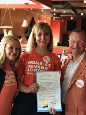 During its 2019 Wear Orange awareness event, Moms Demand Action Members Carin Huffman Grinch, left, and Kristin Bowen accept a proclamation from Columbia Mayor Brian Treece marking National Gun Violence Awareness Day