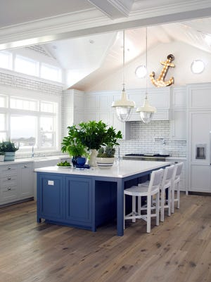 A remodeled kitchen is functional and chic with a large parsons-style island, pale gray-blue Shaker cabinetry and large industrial pendant lights.