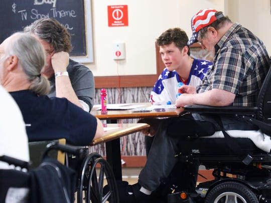 Playing a game of bingo at the Ann Arbor VA Healthcare System are American veterans and Patrick Giles, a player for the U.S. NTDP Under-18 team.