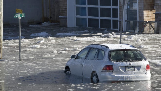 Car of Asbury Park Press photographer Peter Ackerman stuck in flood waters as bay high tide moves in on Long Beach Island.