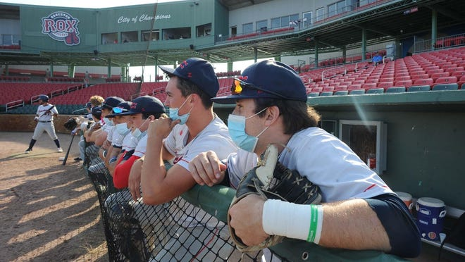 Players watch the Brockton Rox home opener from the dugout on Tuesday, July 7, 2020.