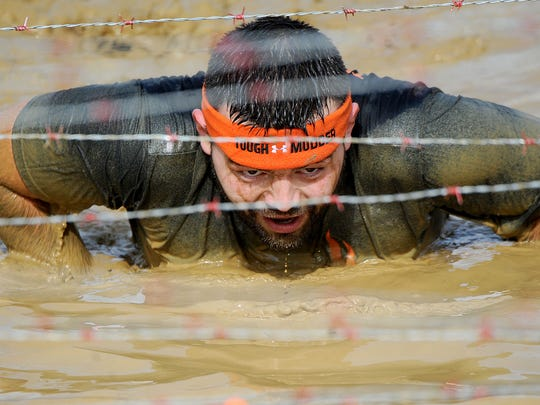 "Jerimy Reed of Newark crawls on his belly as he tackles the ""Kiss the Mud"" obstacle during Tough Mudder Ohio in Lexington on Saturday."