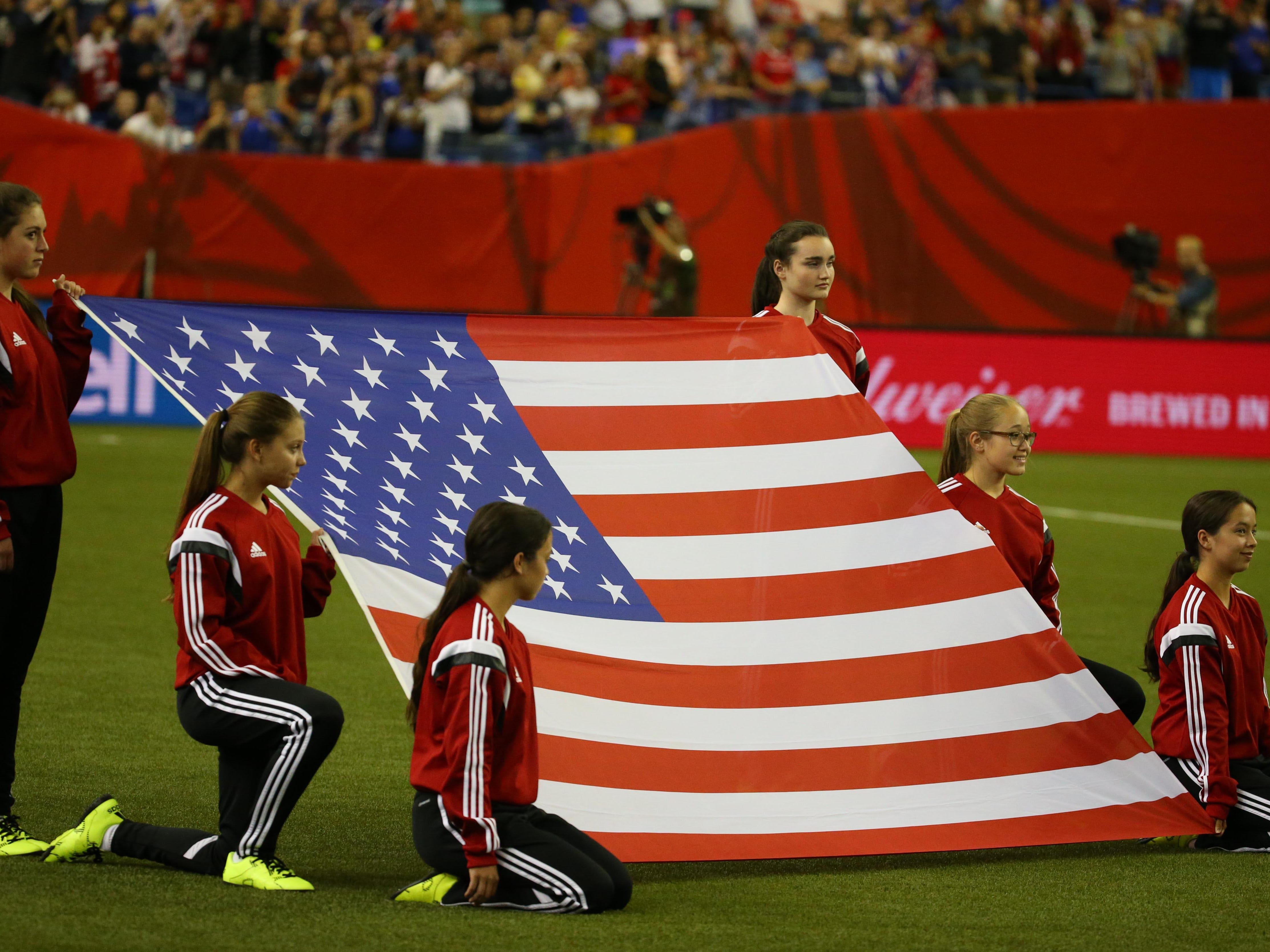 Girls present a United States flag on the field prior to the game against Germany during the semifinals of the FIFA 2015 Women's World Cup.