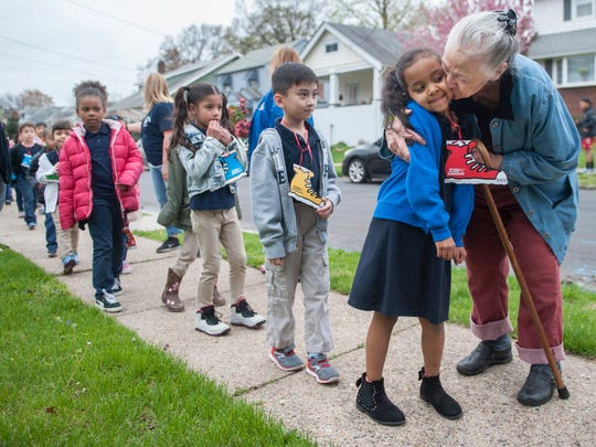 Retired school crossing guard Laura Mason, right, hugs and kisses students of Roosevelt Elementary School in Pennsauken as the students made a surprise visit to Mason's Pennsauken home on Friday, during the school's Walk To Cure Diabetes, to thank Mason for her 50 years of service as a crossing guard.