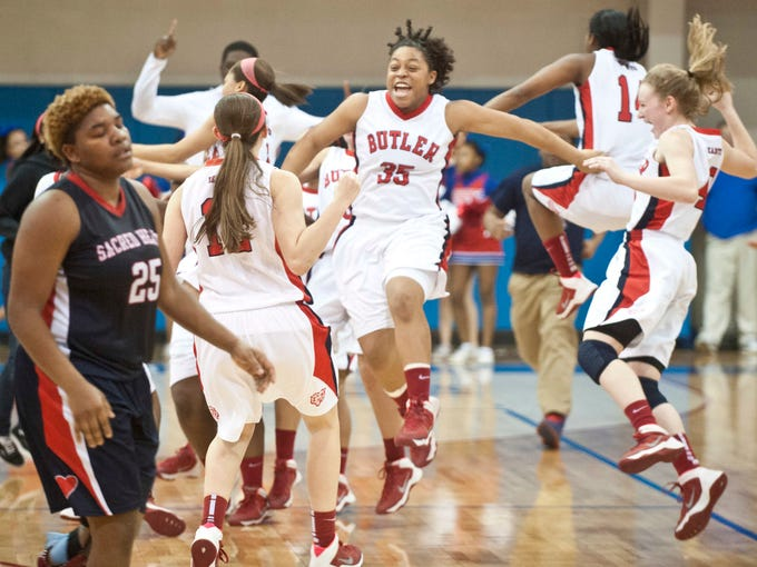 As Sacred Heart Academy Valkyries' forward DaiJia Ruffin, left, reacts to the loss, the Butler Bearettes (including Butler Bearettes' forward/center Janna Lewis, center) celebrate their victory. In a tightly fought battle, Butler edged Sacred Heart Academy, 50-49 to win the 2014 Girls LIT championship. Feb. 01, 2014