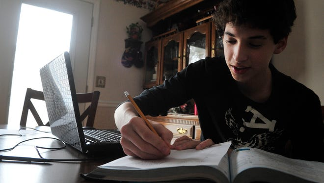 Isiah Stafford, 14, an eighth-grader at West Wilson Middle School in Tennessee, does math homework at the kitchen table. The family uses a computer to do school work.
